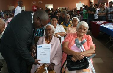 Serina Jordina Speelman and Hester Elizabeth Bruitjies receive title deeds from Minister Bonginkosi Madikizela