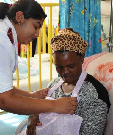 Sister Kajel David (Breastfeeding Champion in Ward B1) showing Ntombekaya Kuse how to use the breastfeeding apron.