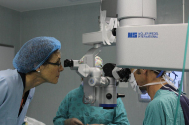 Dr Beth Engelbrecht, HOD for Western Cape Government Health, looks into the operating microscope during a cataract extraction operation.