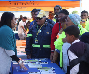 Members of the community listen as Ms Chantell Hendricks (left), of DOCS educates them on the various projects the Department.