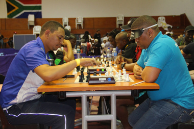 Chess players focus intently on their next move.