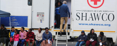 Civilians queue outside the mobile clinic for their turn to be medically assessed by doctors from the University of Cape Town
