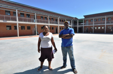 Community Liaison Officer Patricia Beza and Project Chairperson Chris Mntuyedwa in front of the double-storey building.