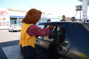 Danny Cat hands out flyers to vehicle occupants.