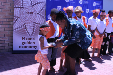 DCAS Minister Mbombo handing  promotional material to learners from Koelenhof Primary school who entertained guest at the launch