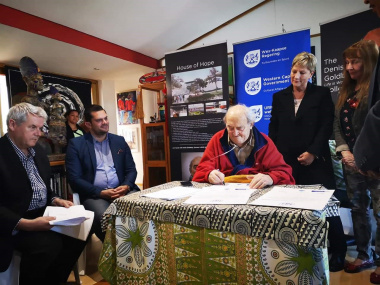 Denis Goldberg signs the co-operative agreement that will enable the establishment of a new education and training centre at the Hout Bay museum
