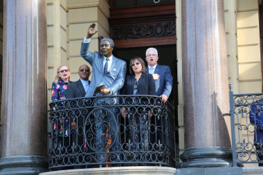 Dignitaries singing the national anthem on the City Hall balcony