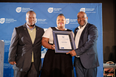 DCAS Director Mxolisi Dlamuka hands over the award to Lwandle Migrant Labour Museum at the annual Cultural Affairs Awards Ceremony