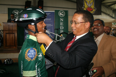 Dr Ivan Meyer puts a helmet on Chadwin Jutzen of Phoenix Secondary School.