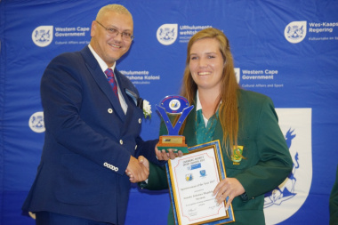 Dr Lyndon Bouah handing over the sportswoman of the year award to Aneke Snyman from Overberg Lawn Bowls.
