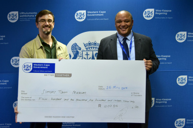 Michael Janse van Rensburg received the ceremonial cheque on behalf of Simon's Town Museum from Guy Redman