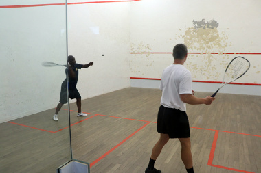 Eager players alternate in striking the ball at the squash court