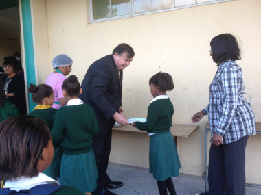 Mr Donald Grant sharing porridge with learners