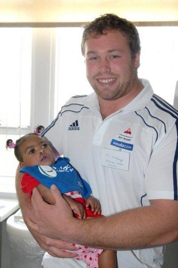 Stormers player JC Kritzinger, holds baby Tamia, who underwent cleft lip and palate surgery at Red Cross War Memorial Children's Hospital. JC took part in the Vodacom Foundation's Tries for Smiles campaign which raised funds for the Smile Foundation