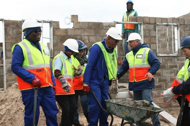 Minister Bonginkosi Madikizela (left) and Western Cape Human Settlements Head of Department Thando Mguli (pushing the wheelbarrow) hard at work at Pelican Park.