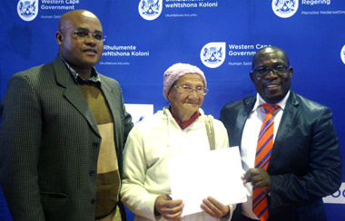 Proud 78 years old Sonia Wiener accepting her title deed from Minister Bonginkosi Madikizela right.