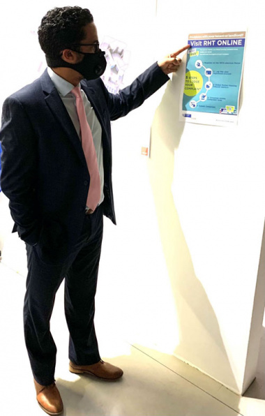 Western Cape Minister of Human Settlements, Tertuis Simmers is pointing to a flyer which explains how to log a complaint online
