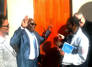 Minister Bonginkosi Madikizela cutting the ribbon that will see Smith entering his new home.