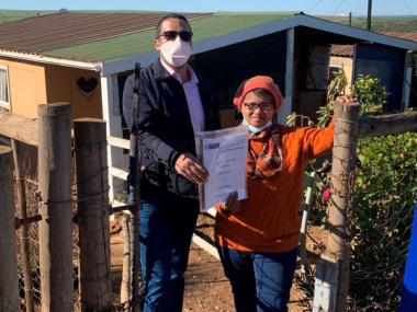 LR - Minister Simmers handing over title deeds to Slangrivier resident Ms Maria Saaiman