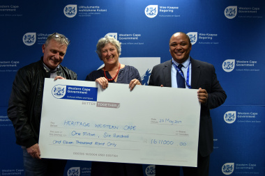 HWC Chris Snelling and Chairperson Antonia Malan receive the HWC payment from Guy Redman