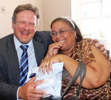 The Western Cape Minister of Health, Mr Theuns Botha, with a patient from Belgravia receiving her medication parcel.