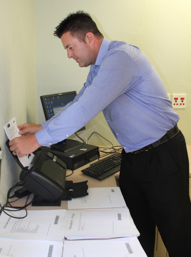 Project Manager Chris du Toit scans one of the patient folders.