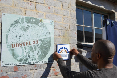 Johathan Windvogel from Heritage Western Cape places the tile on the wall of the Hostel 33