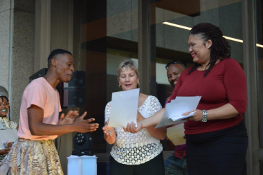 Liezl Jansen (right) and minister Anroux Marais (centre) award certificates to the performers