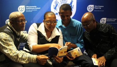 Lungile Fihla (Human Settlements), Nonzwakazi George (Provincial Treasury), Xolisa Tshongolo (DCAS) and Vuyani Nkunzi (City of Cape Town) admire the isiXhosa terminology booklet