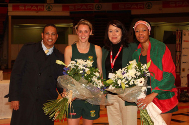 Dr Ivan Meyer with a representative from Netball South Africa and national players Erin Burger and Zanele Ndodana on the occasion of their 50th test caps.