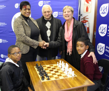 Mercia Sias and Cecil Cupido receiving the chess tables from Minister Anroux Marais.