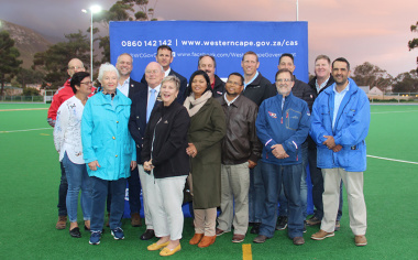 Minister Anroux Marais and stakeholders from the Overstrand Municipality, Hermanus High School, Overberg Sport Council and the WP Hockey Federation under the new floodlights at the synthetic pitch