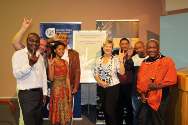 Minister Anroux Marais and other VIPS with the new poster, practising their Sign Language