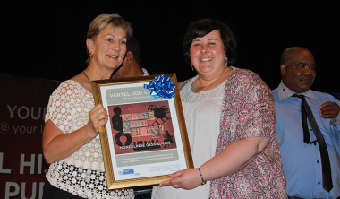 Minister Anroux Marais hands over a framed Oral History Initiative poster to Suzanne Vermeulen from Hartenbosch public library.