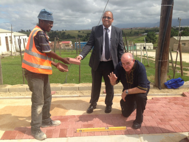 Minister Robin Carlisle, Mayor Standers and a construction worker stand on site in Thembalethu