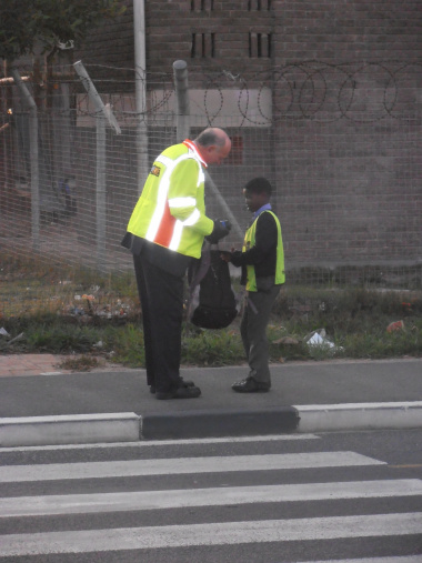 Minister Carlisle assisting an Imbasa Primary School Learner to cross the busy street