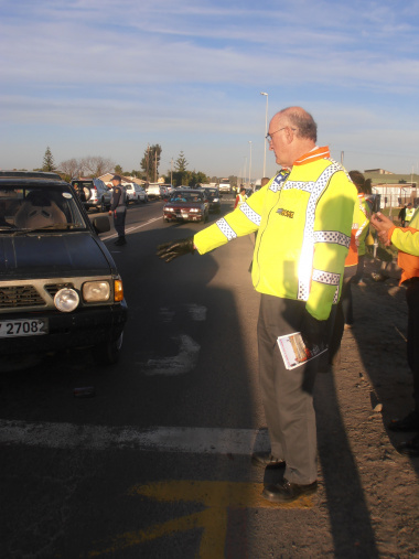 Minister Carlisle directing traffic at the Buttskop Level Crossing.