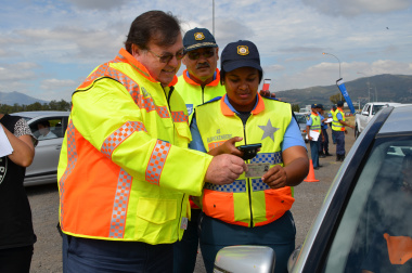 Minister Grant Chief Africa and a traffic officer with the new hand-held device.