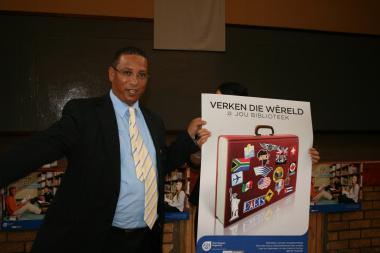 Minister Ivan Meyer accept the newly designed posters by Library Services.
