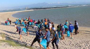 Minister Marais along with WP rugby players and members of the community braved the wind to clean Monwabisi beach.