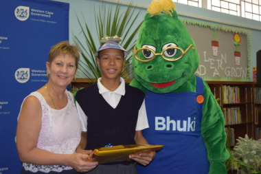 Minister Anroux Marais and mascot Bhuki awarded Joshwin Bizaare for improved reading skills at the afternoon classes at the Monte Rose Library