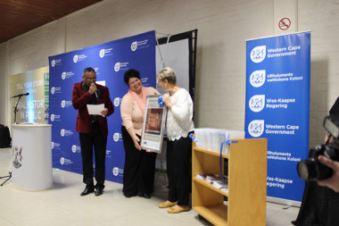 Minister Anroux Marais handing over an oral history poster to one of the library managers at the launch in Worcester