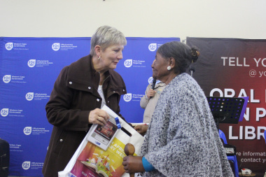 A local storyteller receives the Oral History DVD from Minister Marais in the Community Hall in Mamre