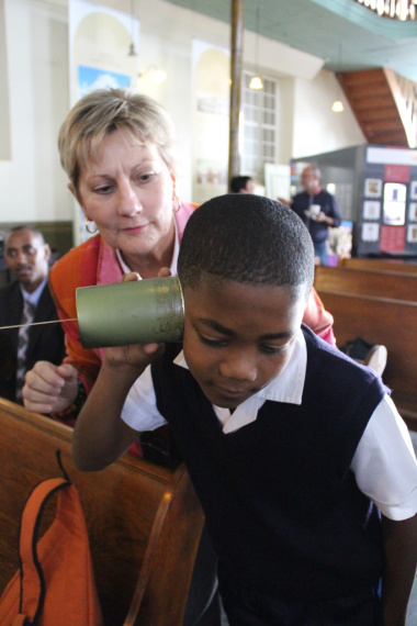 Minister Marais helps one of the learners with the telephone toy