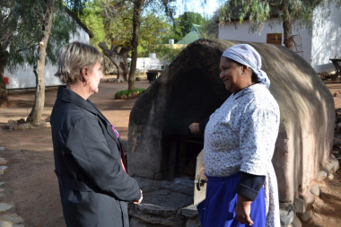Minister Marais learns how bread is baked in the open air oven at Worcester museum