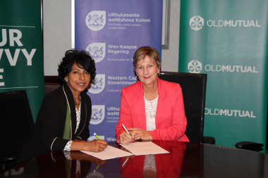 Minister Marais signs the agreement with Helene Africa from Old Mutual