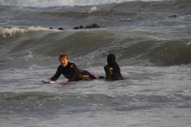 Minister Marais surfing the waves under the guidance of 9Miles project facilitator Nathaniel Stemmet.