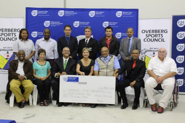 Minister Marais with other DCAS officials and the recipients of the cheque of R430 000