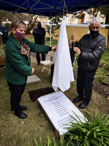 Minister Marias and Dr Isaac Balie unveil the plaque to memorialize the burial of Michael Balie at the Genadendal Mission Museum as the community looks on.