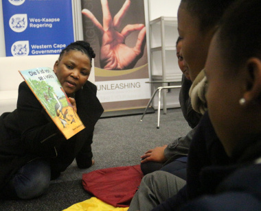 Minister Mbombo engages with learners during an interactive story-telling session.